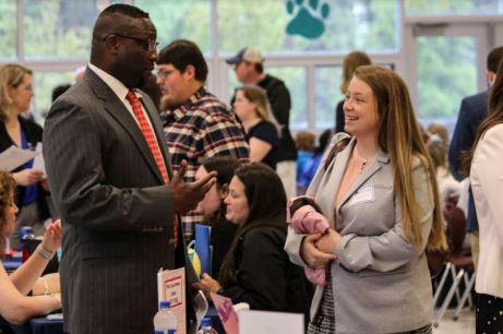 Four Oaks Middle Principal Tol Avery (left) talks with candidate Kayla Strickland (right) at the JCPS Job Fair on April 13 at West Johnston High.