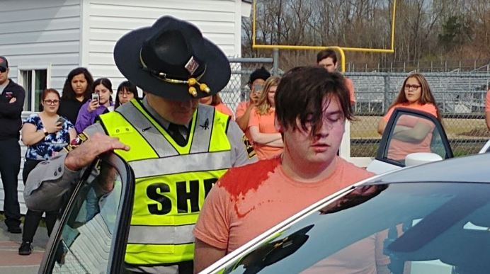 North Johnston High student Trey Allen (right) and NC State Highway Patrol Trooper Chad Sullivan (left) stage an arrest during a mock car accident at the school on March 25.