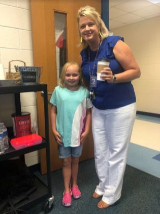 Princeton Elementary student Jenna Williams (left) serves Princeton Elementary Principal Melissa Hurst (right) a cup of coffee from the Pup Cups beverage cart.