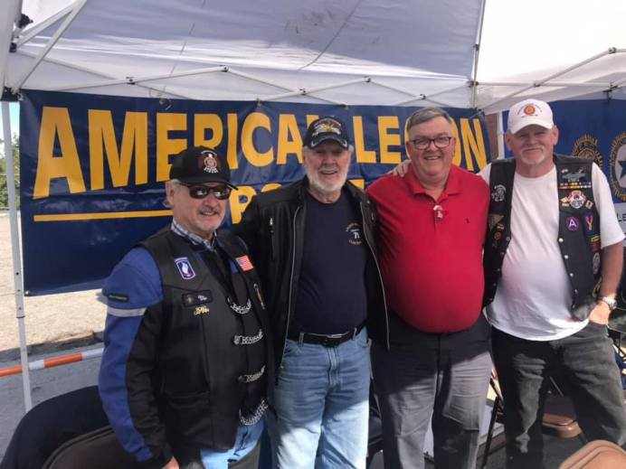 Legion Post 71 members Vic Winn, Bob Gretsinger, Jim Braxton, Sal Pilo in front of the American Legion booth at the Clayton Harvest Festival.