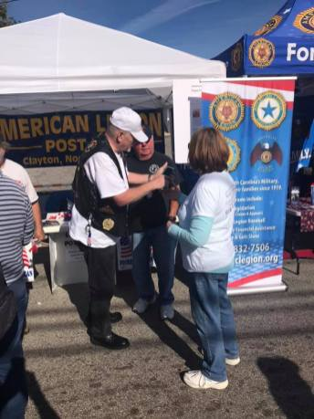 Legion member Sal Pilo explains the American Legion to an attendee at the Clayton Harvest Festival.