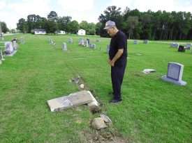 Tony Medlin of Micro looks at a damaged headstone in the Aycock Family Cemetery.