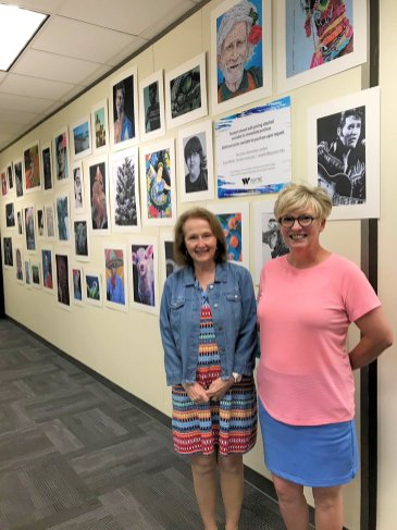 Susan Horne, Rep. John Bell IV's Legislative Assistant, and Wayne Community College Art Instructor Angie Waller pose in front of WCC student art on display outside of Bell's office at the North Carolina General Assembly.