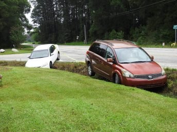 Two cars wait to be towed out of a ditch on NC210 at Swift Creek Road.