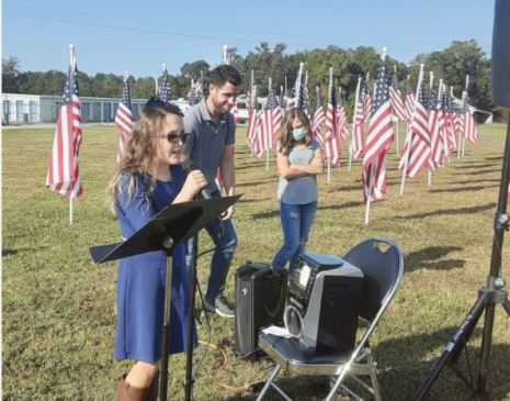 Kaylen Tyson performs the Star Spangled Banner at Saturday's dedication ceremony for the Flags for Heroes field in Angier. Dunn Daily Record Photo
