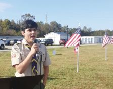 Local Boy Scout Taylor Davenport performs a patriotic tune at Saturday's dedication of the Flags for Heroes in Angier. Dunn Daily Record Photo