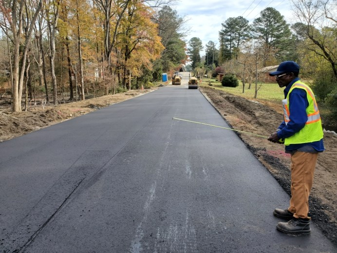 An unidentified NCDOT worker measures the pavement width on Lake Wendell Road.  NCDOT Photo