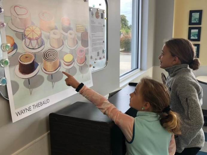 """Caroline and Ellie Saylors enjoy the painting """"Cakes"""" by Wayne Thiebaud located at Mickey's Pastry in Goldsboro."""