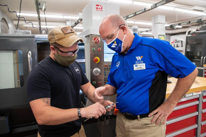 Wayne Community College student Jason Slack (left) and his Computer Integrated Machining instructor David Meek check the precision of a part milled in one of the college's machines. As many WCC courses as possible are moving completely online but all that have had face-to-face components have been required to follow protocols like mask wearing.
