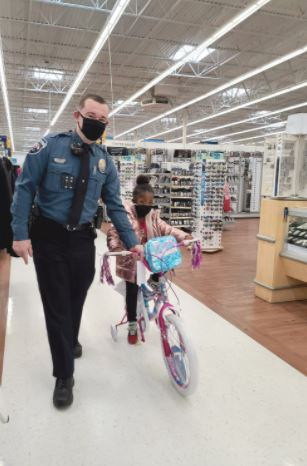 Three-year-old Eve Halsey rides her new bicycle as Dunn police Officer Christian Grant holds on during Shop with a Cop Tuesday morning. Dunn Daily Record Photo