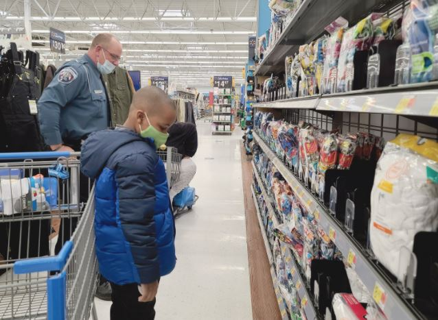 Seven-year-old Quentin Parker looks for Christmas gifts with Dunn police Officer C. S. Keon at the Dunn-Erwin Walmart Tuesday morning. Dunn Daily Record Photo