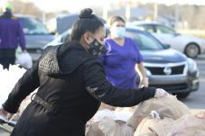 School Nutrition Free and Reduced Data Processor Glenda Andrade helps distribute Holiday Meal Kits at Smithfield-Selma High.