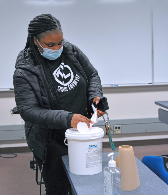 Wayne Community College student Shaudrella Harvey grabs a sanitizing towelette so she can wipe off her desk before the in-person component of a hybrid course begins.