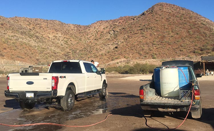 Dry RV Camping on Santispac Beach, Bahia Concepcion, Baja California Sur, Mexico. The men use a water pump hooked to their truck battery to wash your vehicles