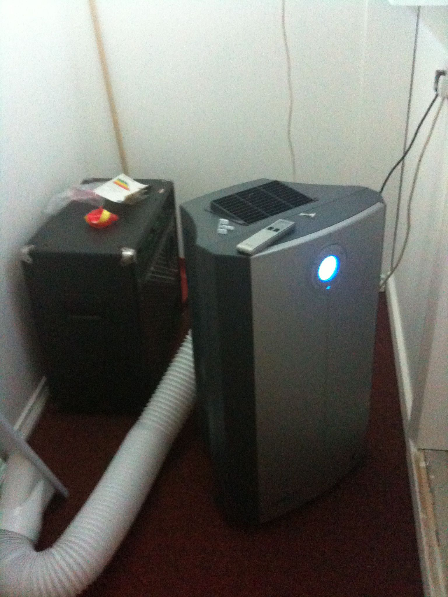 Aircon unit with exhaust pipe. And a blank wall.