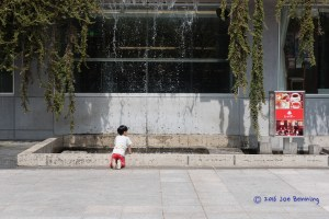 Boy Playing by Waterfall Pool in Tenjin Park