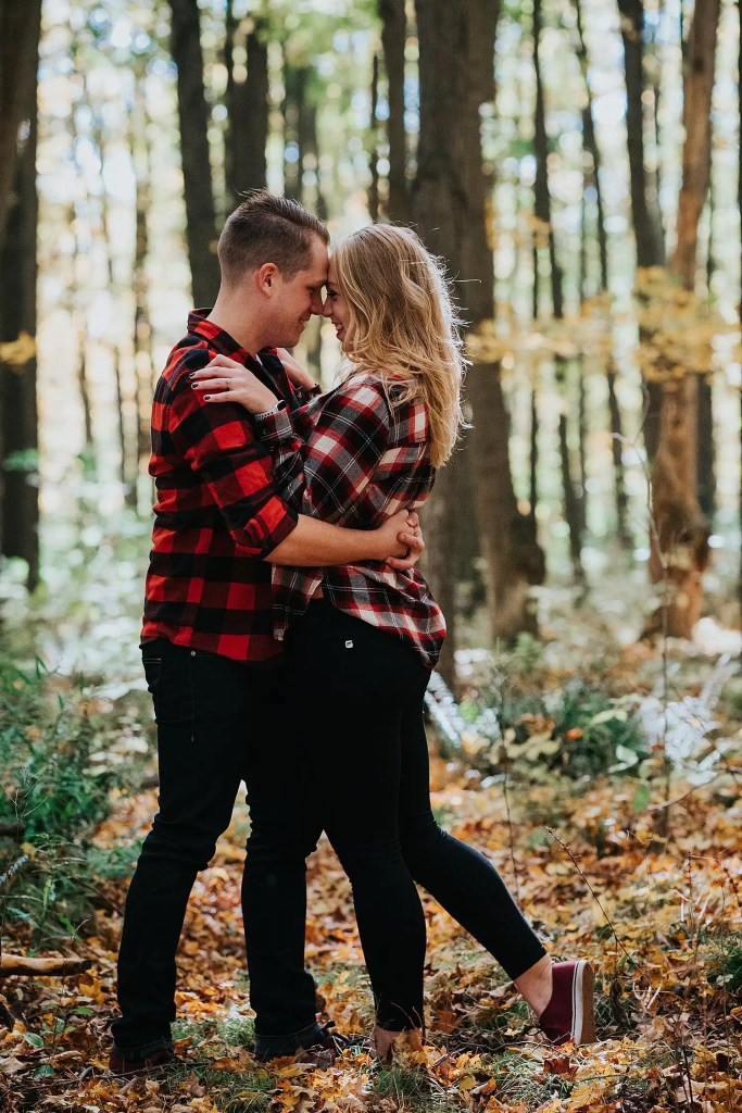 engaged couple going for a kiss in the woods