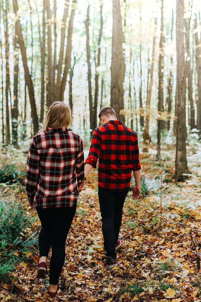 couple holding hands and walking in the woods