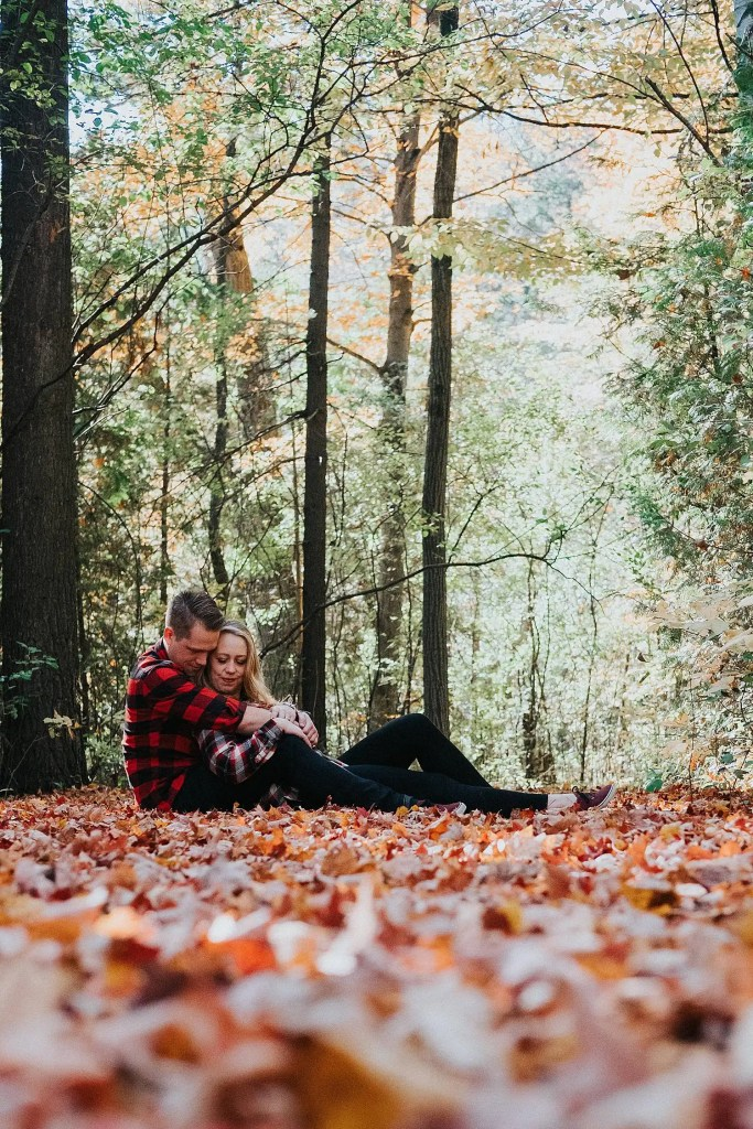 couple sitting on a pathway surrounded by fall leaves