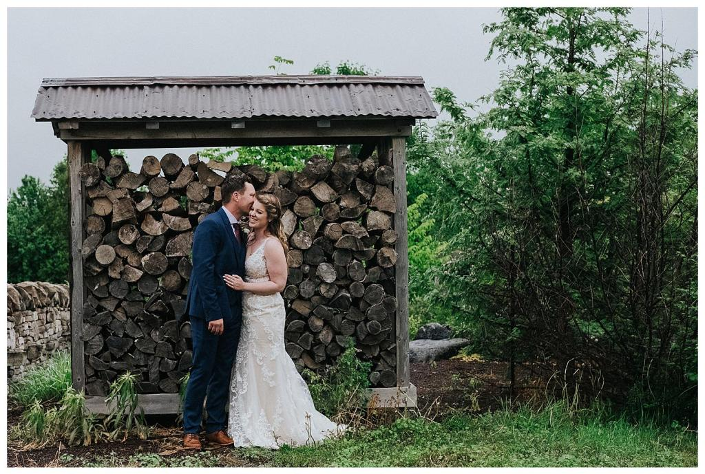 Wood piles make the best backdrops | Rainy wedding photo ideas
