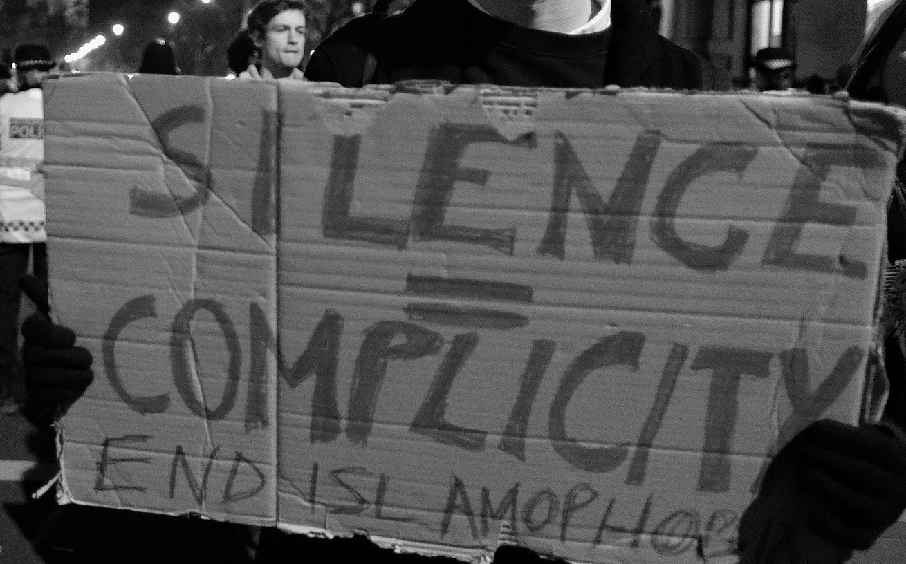 Protest sign: 'Silence = Complicity'