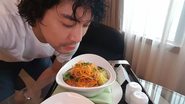 Me enjoying the aroma of my oriental noodles soup that I ordered from room service.