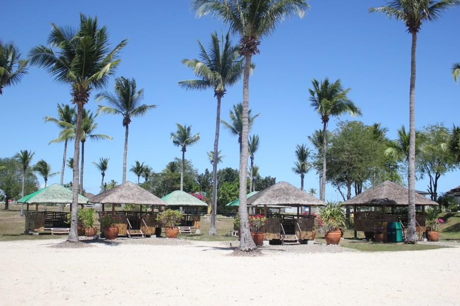 Huts by the beach in Tamarind Cove, Porto Laiya