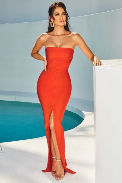 woman in front of pool in orange bandage maxi dress
