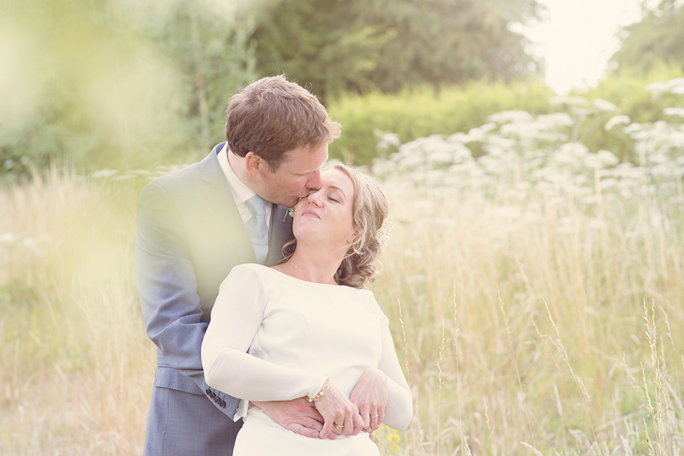 Bride and groom kissing in a summers field, investment