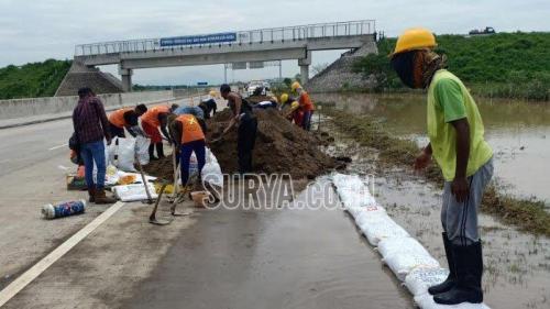 Pekerja memasang tanggul sementara dari sandbag di Jalur Tol Surabaya Madiun di KM 603800 604200 jalur B Jumat 8 3 2019 siang.