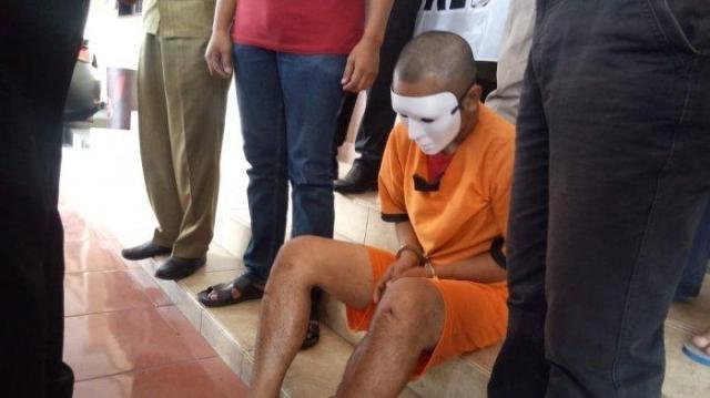tersangka pembunuh nenek iyah 60 berinisial aa 20 terduduk dan memakai topeng