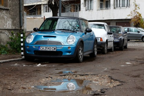 Row of parked cars in a side alley full of potholes.
