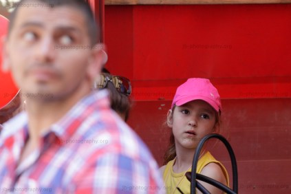 Little girl behind a bodyguard looking up to a speaker on the podium.