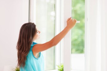 Woman with improved air quality from John Betlem Heating and Cooling, Inc. looking out window.