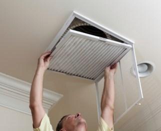 John Betlem Heating and Cooling, Inc. technician installing air filter.