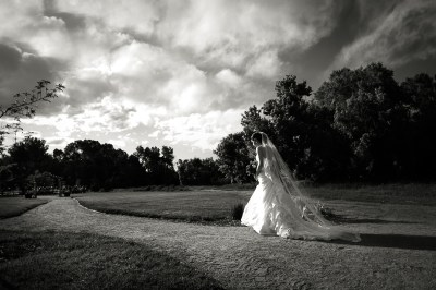 dramatic black and white image of bride walking down aisle with clouds at chatfield botanic gardens wedding