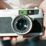 two hands holding a vintage film camera