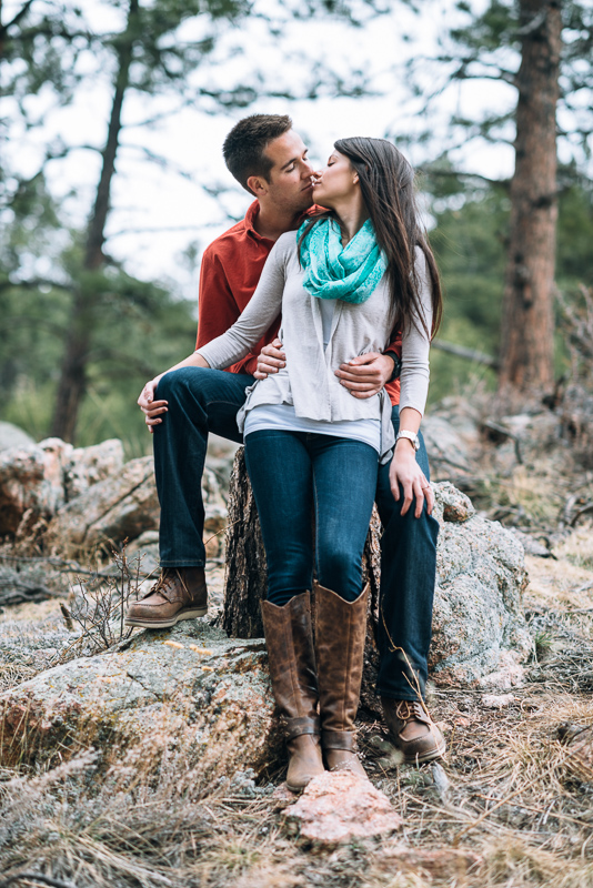 Evergreen engagement photography kissing couple in a forest