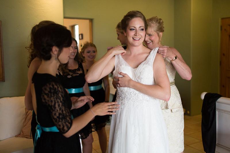 Golden Wedding Photographer bride putting on ress