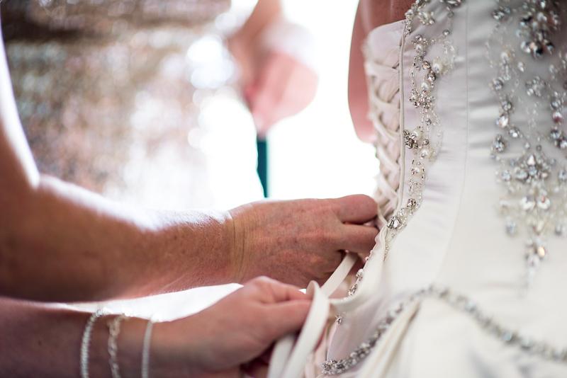 denver wedding photography putting on dress