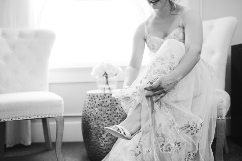wedding bride putting on shoes black and white