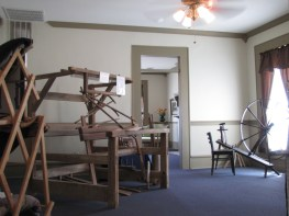 A loom and a spinning wheel upstairs in the Lloyd Tilghman House & Civil War Museum.