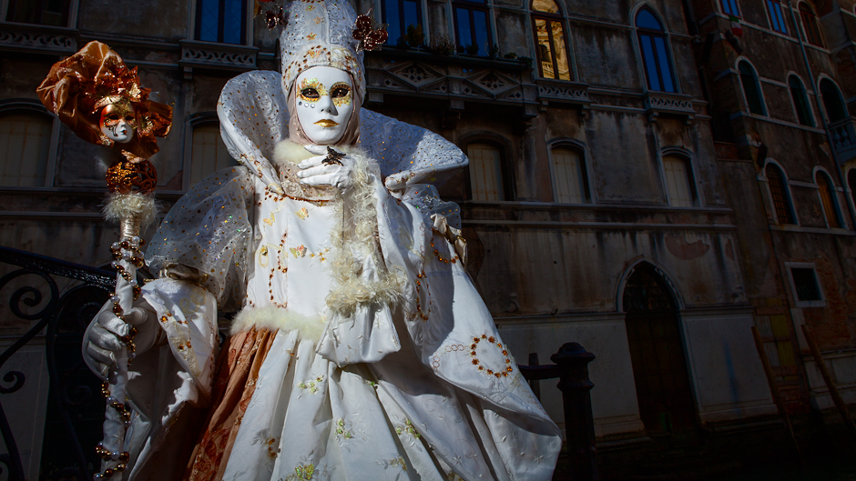 Costumed reveler in white fantastical costume in Venice lit by flash