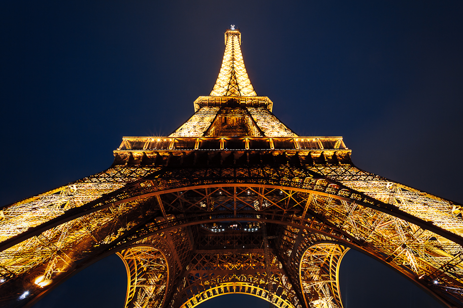 A photograph of the Eiffel tower in paris, shot from below, looking up in the early night