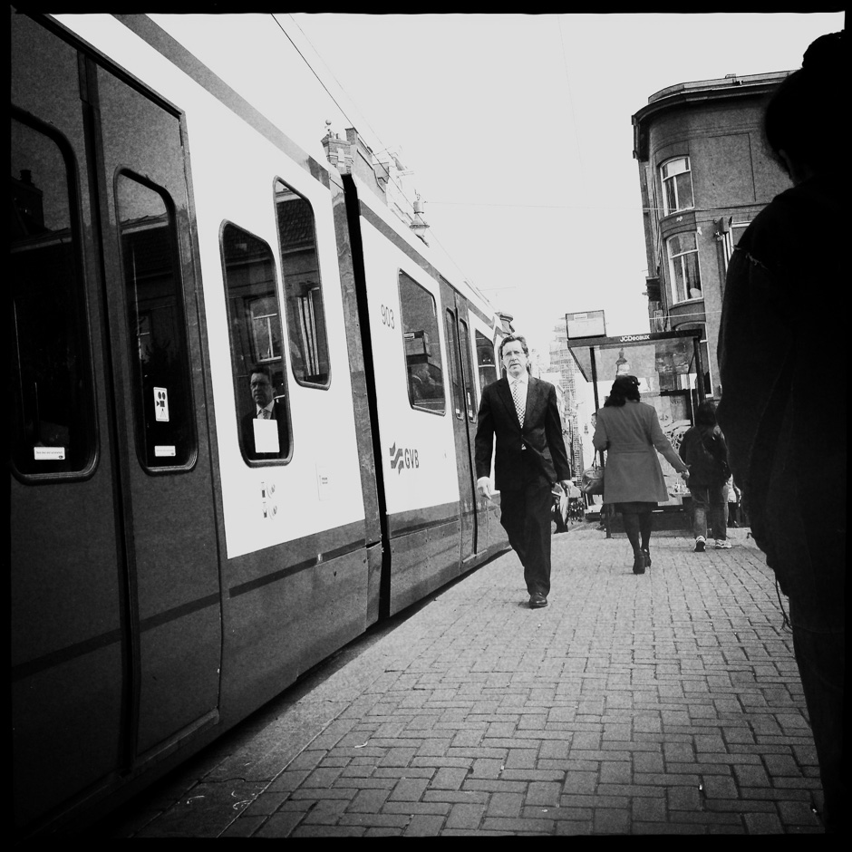 Black and white photograph of a man walking next to a Tram in Amsterdam taken with the iPhone and Hipstamatic