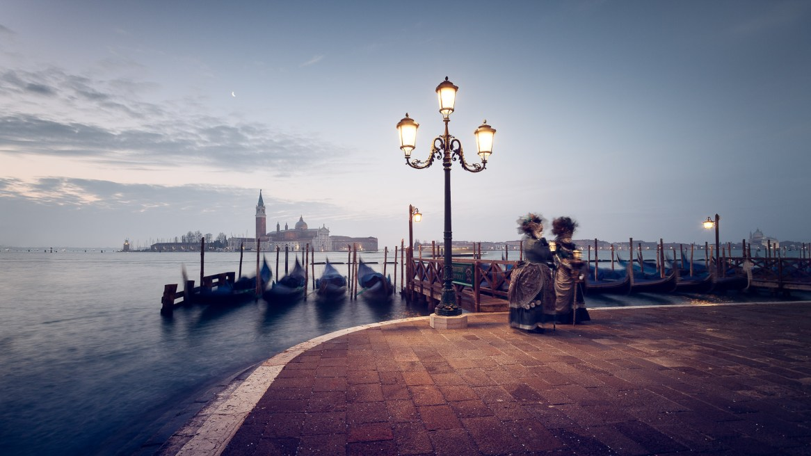 A couple of masked and costumed carnival attendants pose for photographers at sunrise in venice