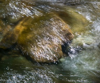 Sunlights draws crazy scribbles as it pours over rocks in Fargo Brook