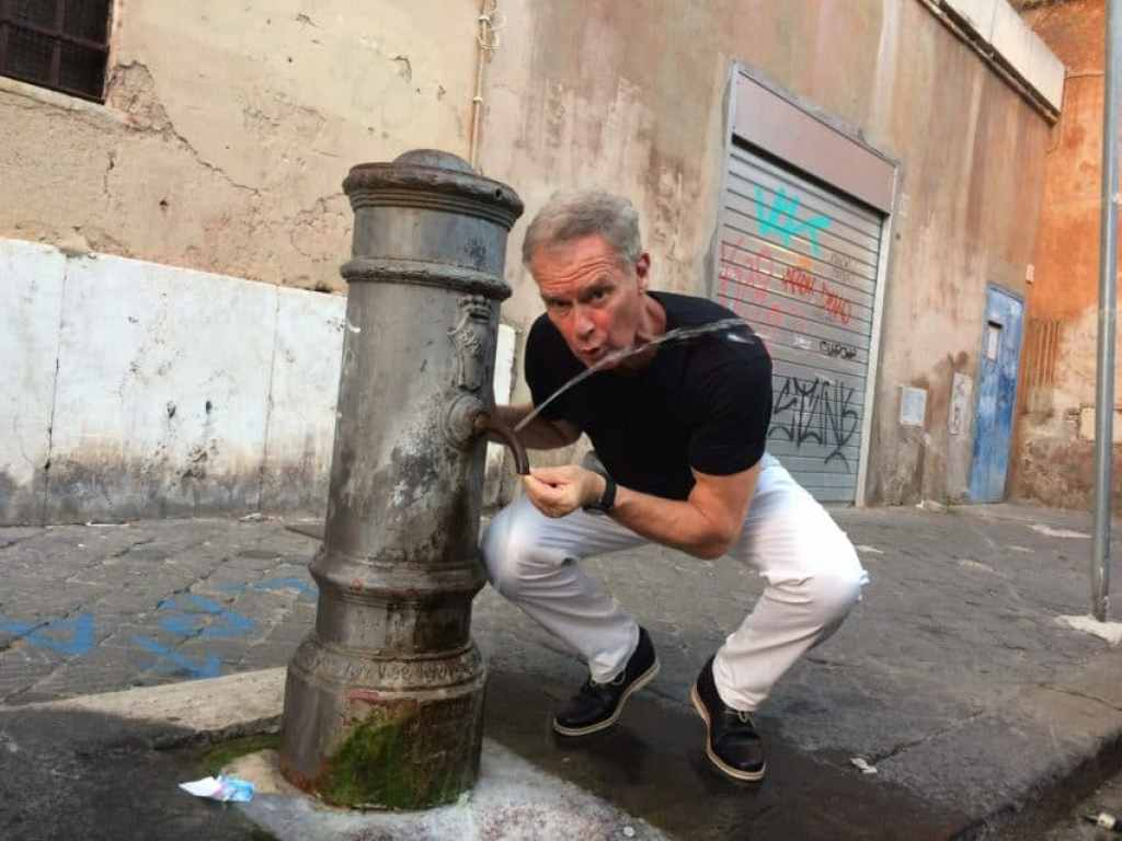 """Me at one of the """"nasoni"""" in steaming Rome. The city has 2,500 of them but the water shortage has closed 400. Photo by Marina Pascucci"""