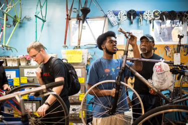 Marsalis Johnson, center, a former intern and now mechanic, assists a customer at Street Level Cycles a part of Waterside Workshops in Berkeley, California, February 20, 2015.