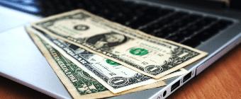 Laptop computer with dollar bills